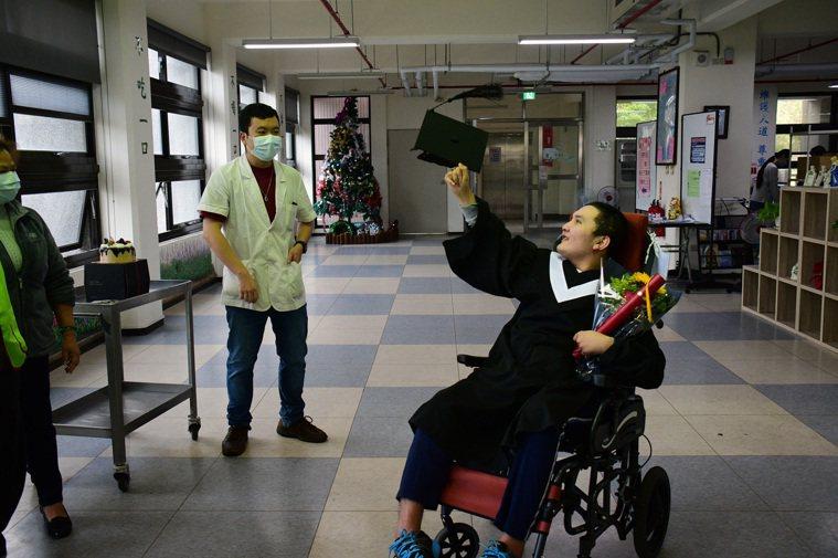 嘪姓男子試著努力拋起學士帽,卻因力氣不足無法成功。記者施鴻基/攝影