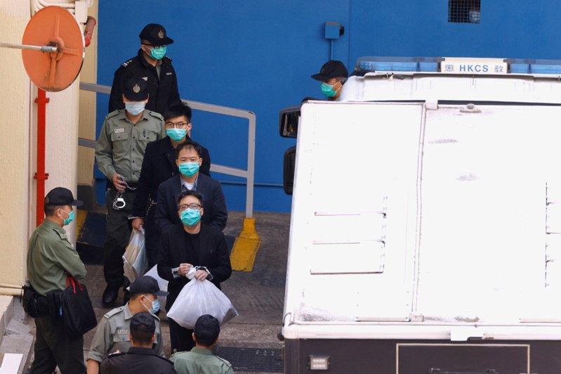 前香港眾志秘書長黃之鋒(後三起)、民主黨前主席胡志偉和人民力量副主席譚得志,在警員戒護下步出監獄前往法院開庭。(路透)