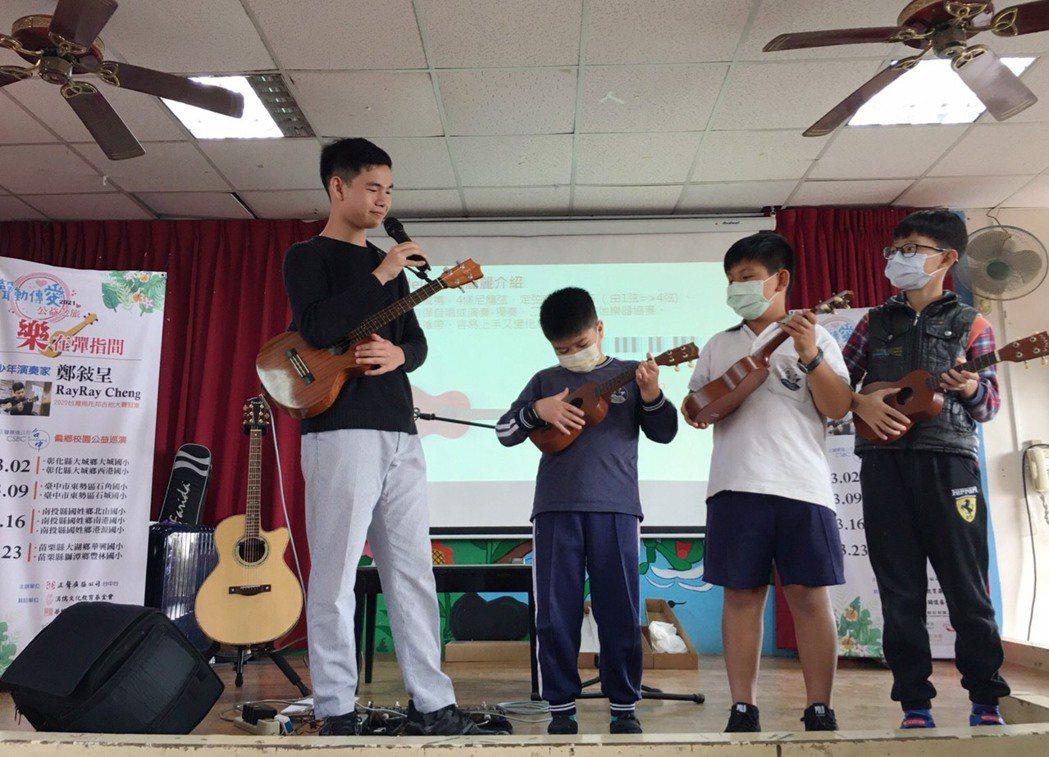 鄭敍呈RayRay(左)指導小朋友體驗彈奏烏克麗麗。 正聲/提供