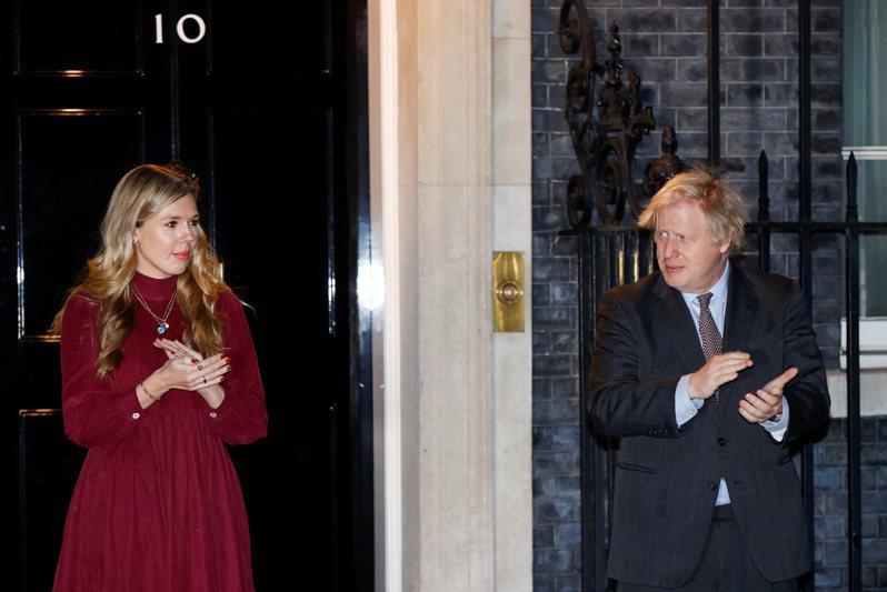 英國首相強生(右)的未婚妻席孟茲(左)重新裝潢唐寧街11號首相官邸的花費嚴重超支。圖為兩人2月3日在官邸前現身。路透