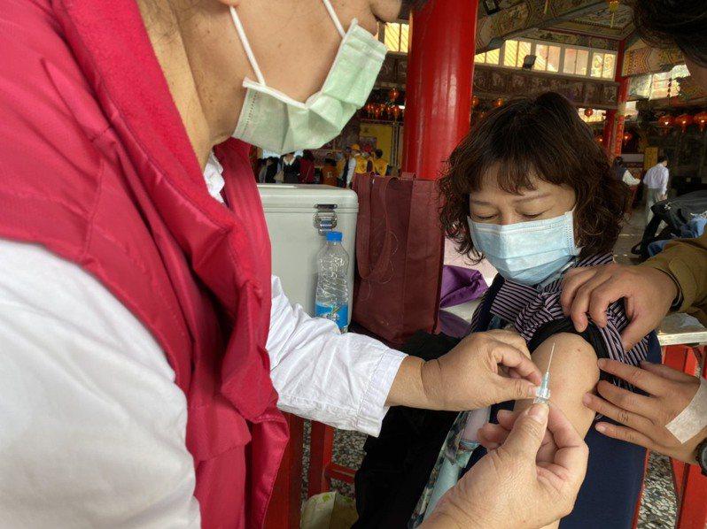 雲林縣台西衛生所到廟宇設站催打流感疫苗,但效果有限,一名從未接種過的志工不忍衛生所人員壓力大,忍痛接種。記者陳雅玲/攝影