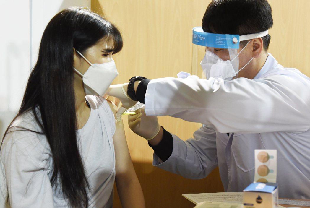 南韓3日在四處地方預防接種中心啟動輝瑞疫苗施打作業,圖為一名醫護人員接種輝瑞疫苗...