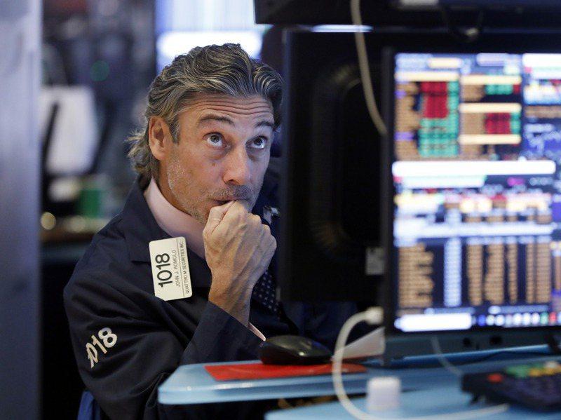 美公債殖利率竄高,風險資產重傷。圖為紐約證交所交易緊盯股價波動。美聯社