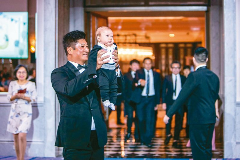 去年十一月底,辜仲諒宴請娶媳、孫子滿月酒,開心地手舉愛孫,滿臉笑意。圖/中信慈善基金會提供