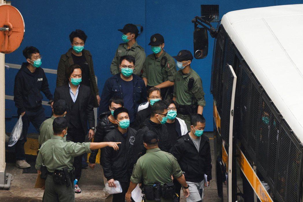 香港47名民主派人士被指控「串謀顛覆國家政權」。圖為3月4日,岑子杰、郭家麒、林卓廷及陳志全等人步上囚車前往法庭。 圖/路透社