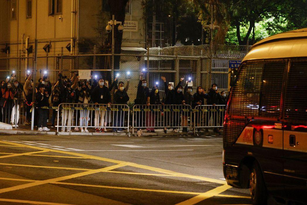 3月3日晚上,搭載被告的囚車駛離西九龍裁判法院,民眾在路旁點燈聲援。 圖/路透社