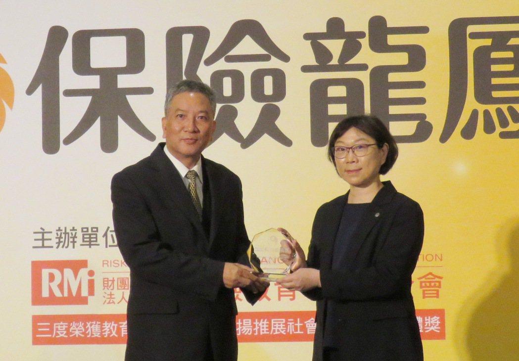 臺灣產物保險公司副總經理許乃權(左)代表,接受金管會保險局副局長王麗惠頒獎表揚。...