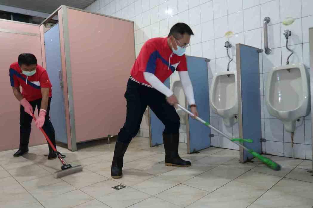「會計師好強會」會長蔡家龍(右)親手打掃療養院廁所。 李炎奇/攝影