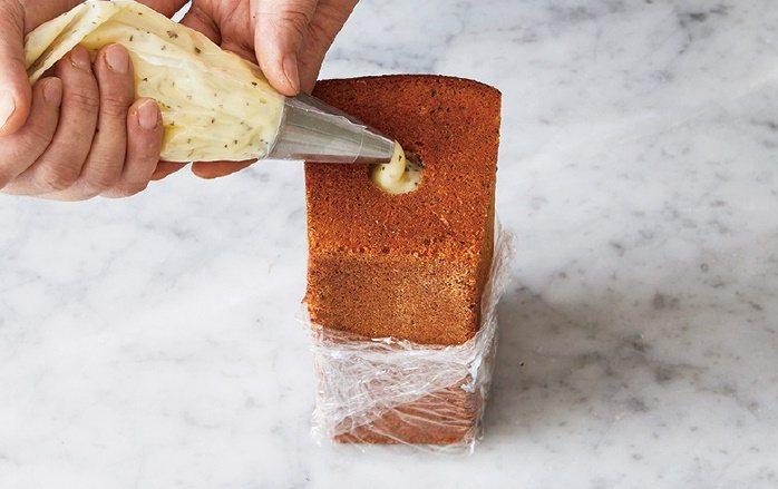 利用擠花袋將事先做好的羅勒甘納許擠進磅蛋糕的孔洞。 圖/台灣廣廈 提供