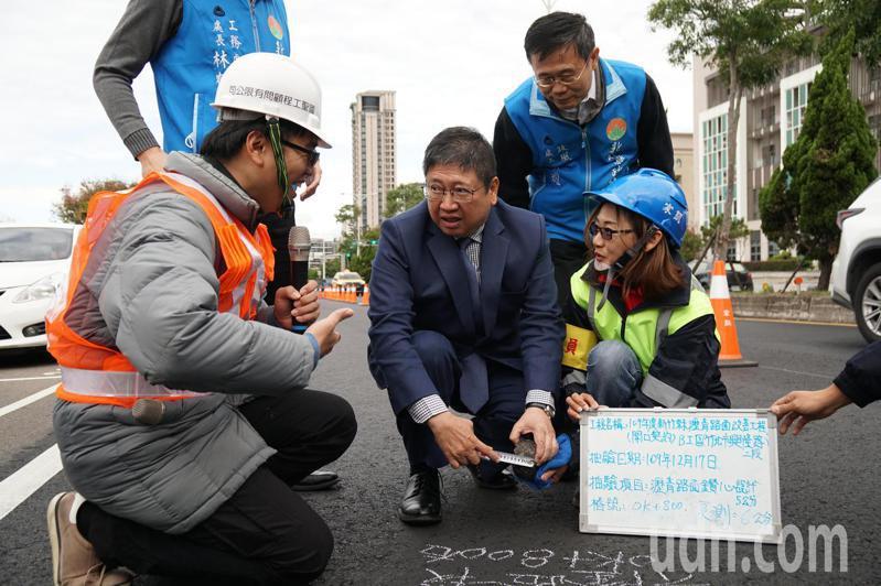 新竹縣長楊文科在興隆路2段新竹地方法院前路段,以捲尺量測鑽心取樣的瀝青厚度。本報資料照。記者陳斯穎/攝影