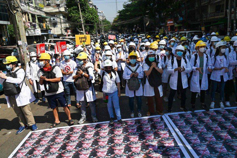 仰光的醫護人員與學生五日在街頭抗議軍事政變,地上是軍頭敏昂萊的肖像組圖,全部被打叉。(法新社)