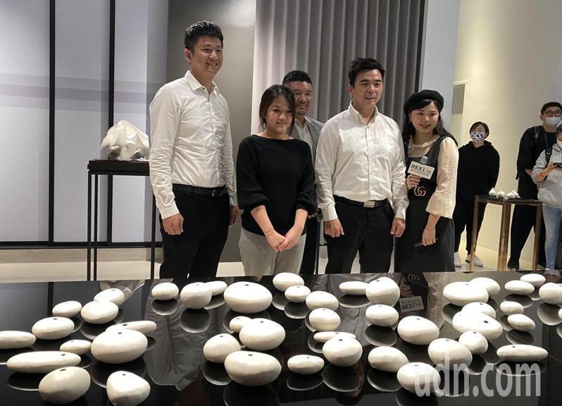 藝術家邱俞鳳(左二)介紹,作品「「卵石」看似一顆顆河床上的卵石,其實是以白瓷土手捏而成。記者趙容萱/攝影