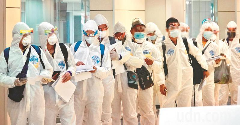 圖為身穿隔離衣的入境旅客,等待檢疫。示意圖。本報資料照片