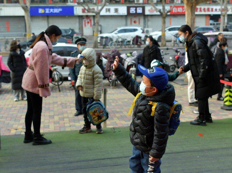 中國河北省石家莊市藁城區今起解除區域封閉管理,圖為8日,河北石家莊市某幼兒園外,一名小朋友和家人揮手道別。 中國新聞社