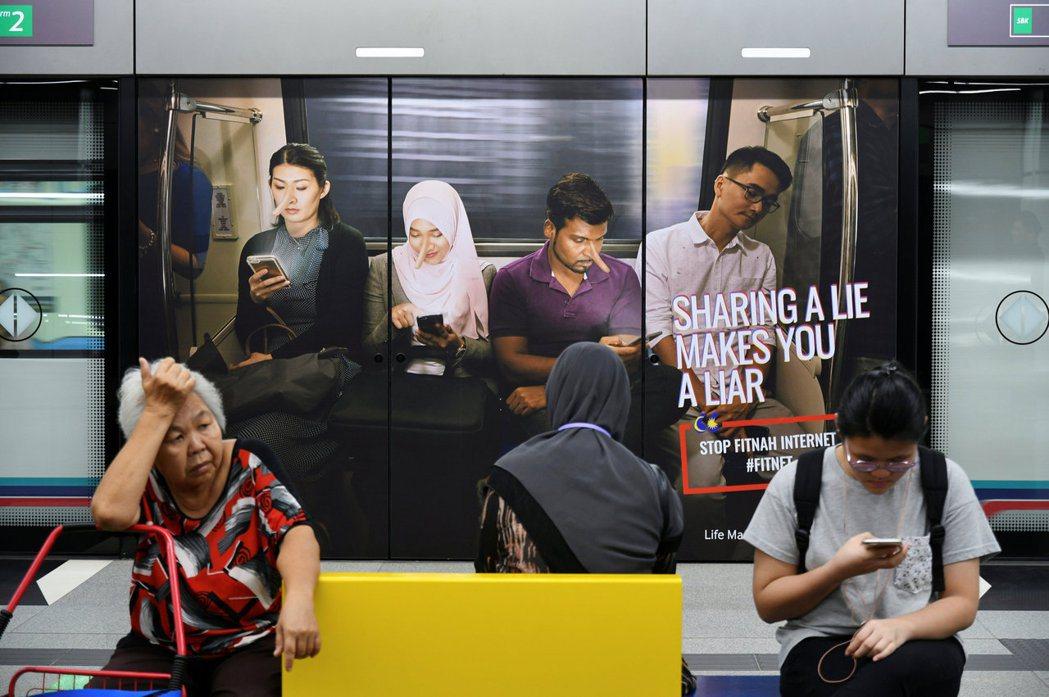 時任首相納吉在2018年4月通過《反假新聞法令》,圖為當時的吉隆坡捷運站裡向民眾...