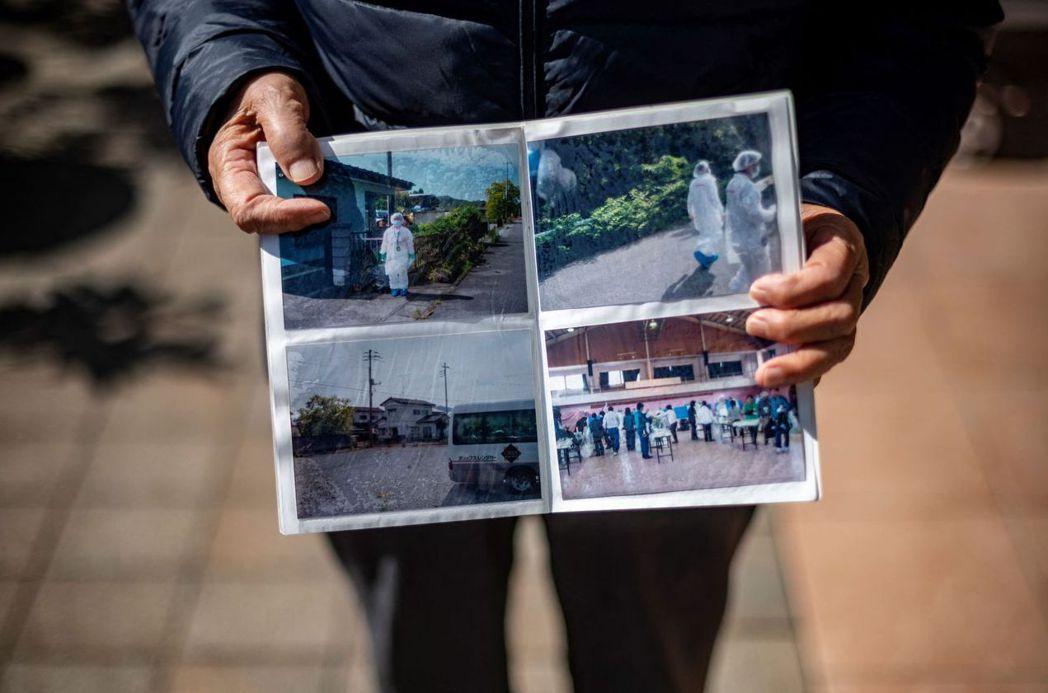圖攝於2021年2月28日,民眾展示福島第一核電廠發生核災後的照片。 圖/法新社