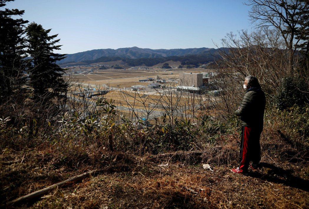 圖攝於2021年2月28日,民眾在311大地震10週年時,望向以前居住的社區。 圖/路透社