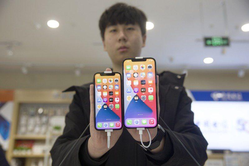 中國大陸一家商場工作人員展示蘋果iPhone 12 mini(左)和iPhone 12 Pro Max(右)手機。  中新社