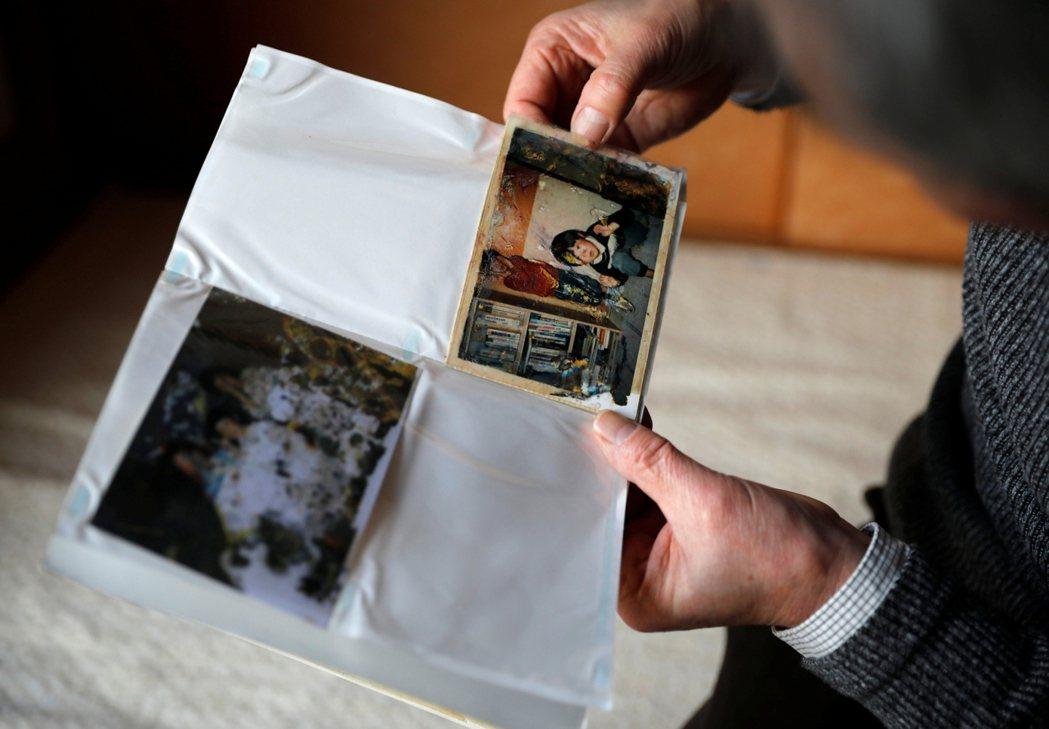 岩手縣陸前高田市,一名老人看著震災逝去的親人相片。 圖/路透社