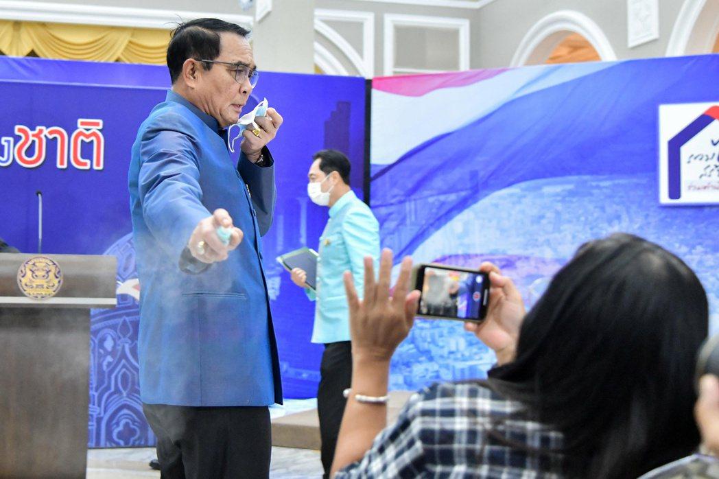 泰國總理帕拉育9日在泰國政府大樓拿起講台上一瓶酒精消毒液朝記者噴。(路透)