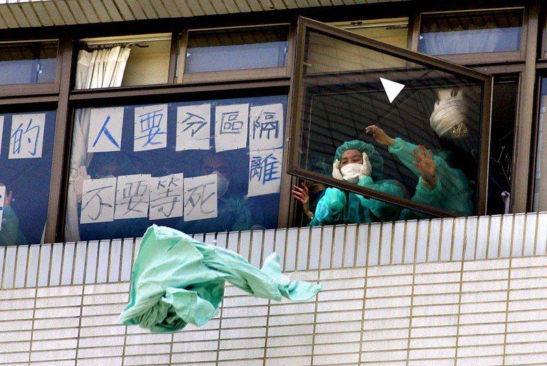 2003年台灣在SARS疫情期間,和平醫院SARS疫情持續升高,B棟7樓的病患家屬不滿被隔離,丟床單抗議。圖/聯合報系資料照片