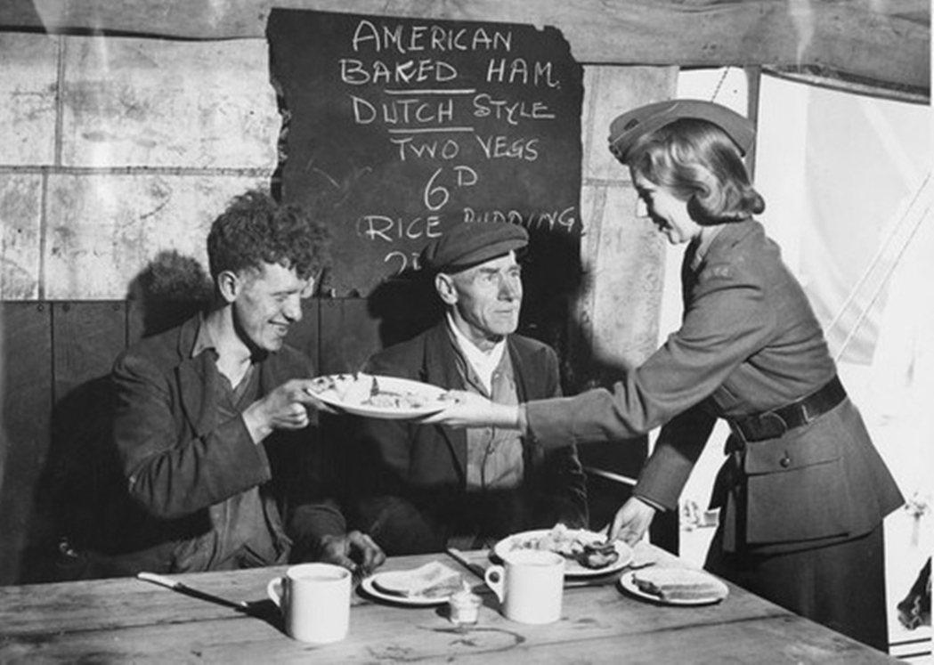 1941年,兩名利物浦工人在吃由美國提供的食物。 圖/英國帝國戰爭博物館