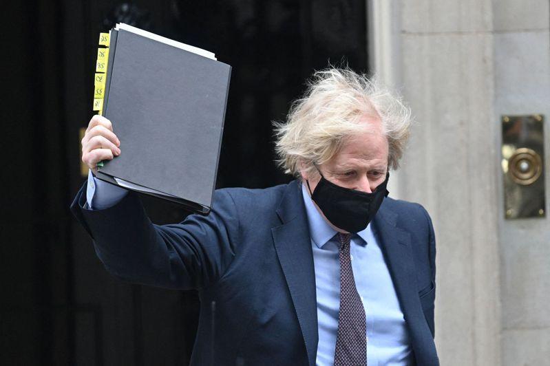 英國首相強生十六日離開首相府,準備向國會簡報新的外交政策大綱。(法新社)