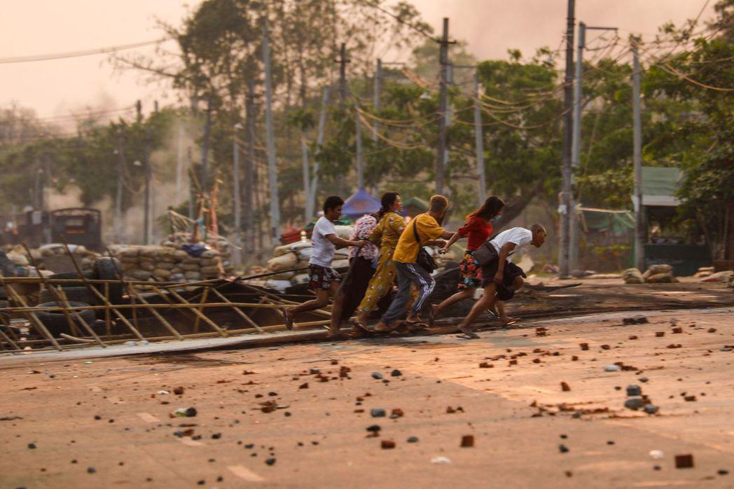 圖為3月14日安全部隊在萊達雅區鎮壓期間,民眾快速越過示威者設置的路障。 圖/法...