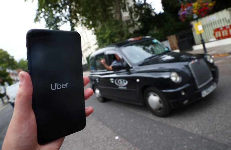叫車平台Uber同意將英國的7萬名駕駛列為公司的勞工(worker)。圖為一名倫敦人用Uber叫車。路透