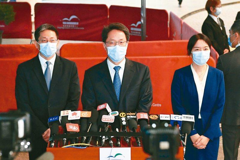 大陸港澳辦副主任張曉明(中)昨天明確表示,香港區議會應回到基本法原先規定的地區事務諮詢機構性質。(中新社)