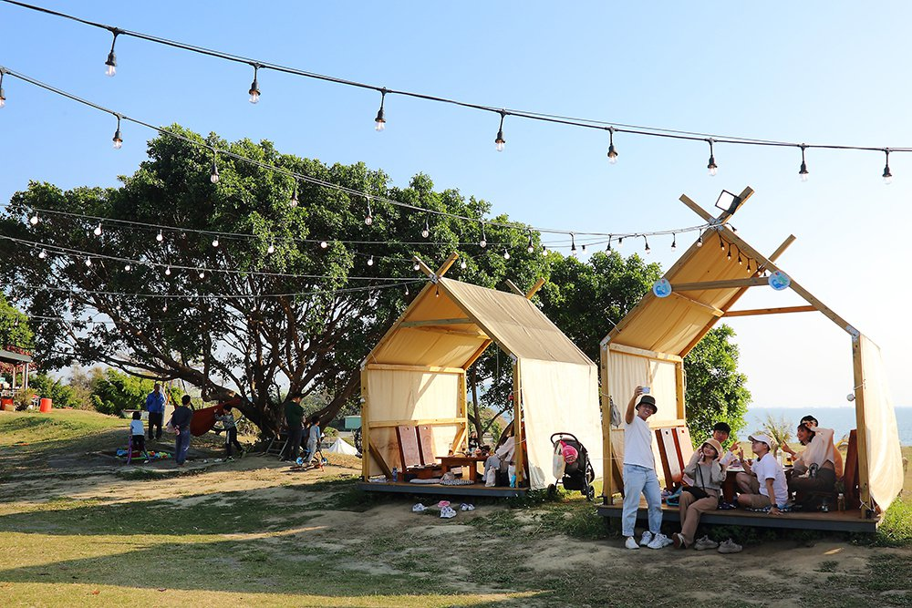在帳篷棧板欣賞一望無際的草地和海景,彷彿擁抱全世界,讓心情也跟著飛揚。  圖/...