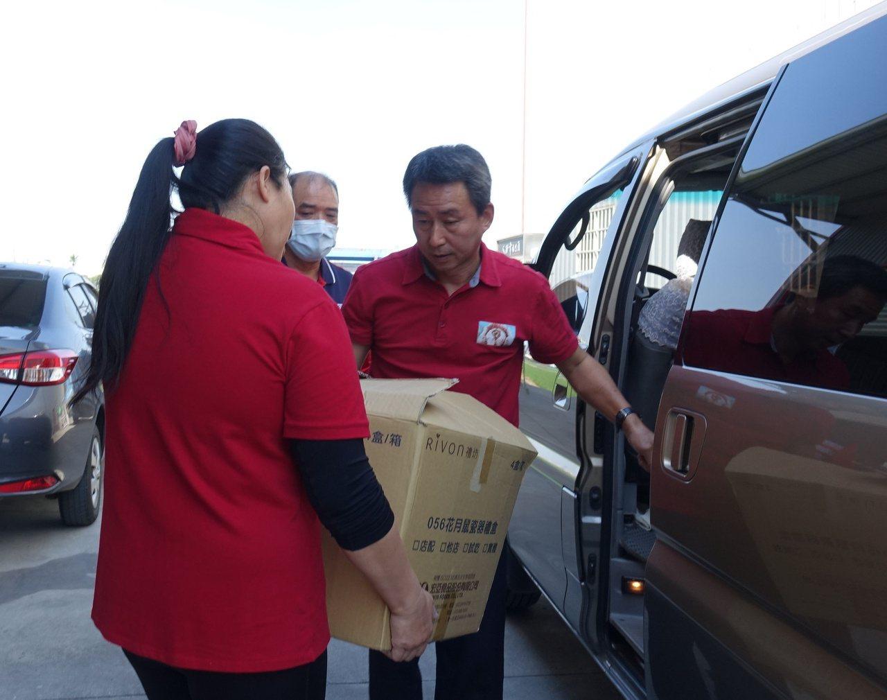 網路「炭火愛心平台」負責人鄭國華(右)幫忙把愛心物資搬上載連物資的團體車上。 圖...