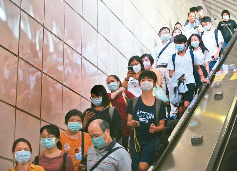 國內疫情急劇升溫,已經進入社區感染。圖為民眾搭乘捷運配戴口罩。報系資料照