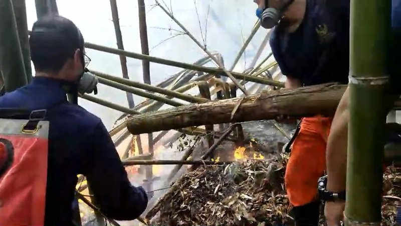 消防局派遣消防人員與當地部落居民合作開闢防火巷,等待直升機灑水滅火。 圖/新竹縣消防局提供