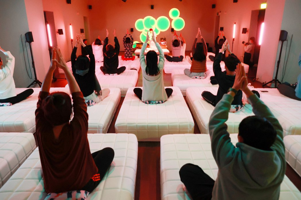 參與者躺在床上,平靜心情、調整氣息,跟著老師透過瑜珈,伸展與放鬆肢體。 林伯東/...