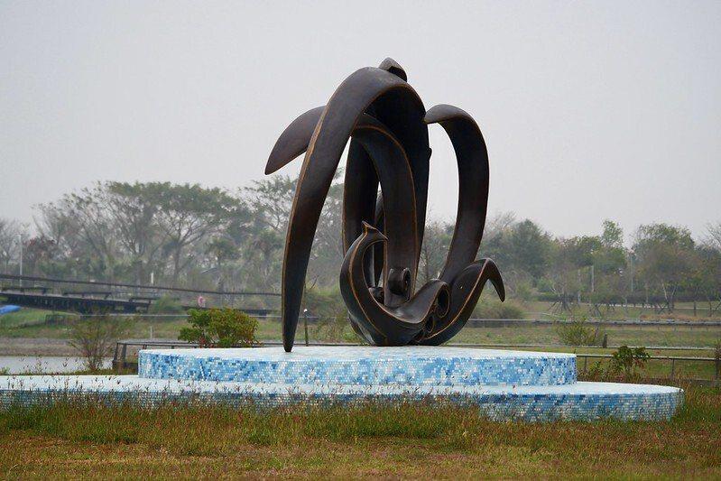 蒲浩明作品《鳳點水》:作者以鳳凰隱喻東方文化體系裡的完美化身,翻飛的尾羽,凌空劃出一個生動的迴圈,既似浪潮翻騰,亦如暖巢安居。在垂蔭楊柳之間,鳳尾滴點湖水,傳達了神鳥鳳凰以靈氣雨露均霑、澤被大地的吉祥象徵。作品融合運用了西方『量塊』和東方『線條』的雕塑美學,透過本件作品遙望園區外之嘉南平原,更意寓了國際/亞洲與臺灣之交流與接軌。(故宮網頁公開資訊)