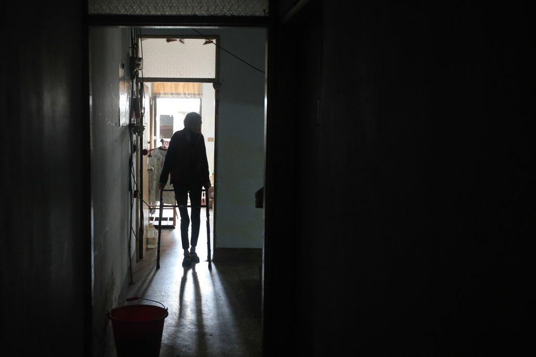 劉蔭拄著助行器站在雅房門口,從走廊盡頭望去,受骨如柴的背影,居服員擔心她又跌傷,...