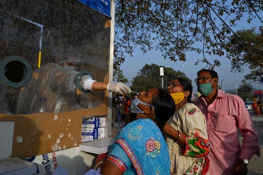 在正在進行的大佛節期間,一名醫護人員替參與者進行快篩。 圖/法新社