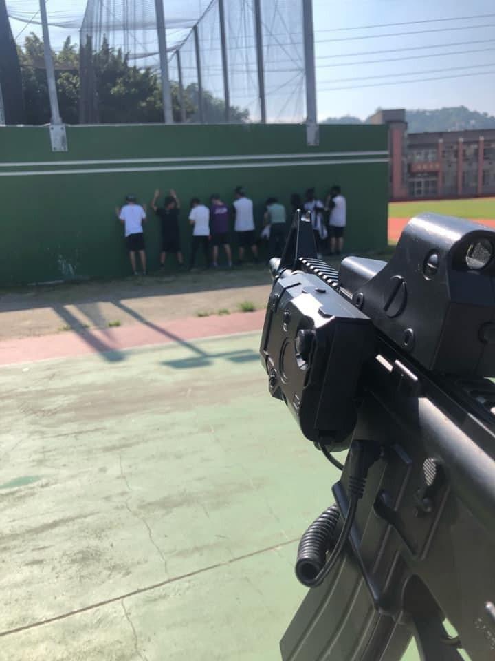 台中一間高中學生持水彈槍,對著站在牆邊的同學作出類似「處決」的動作,影片曝光後,引發網友熱議。圖/翻攝自爆料公社