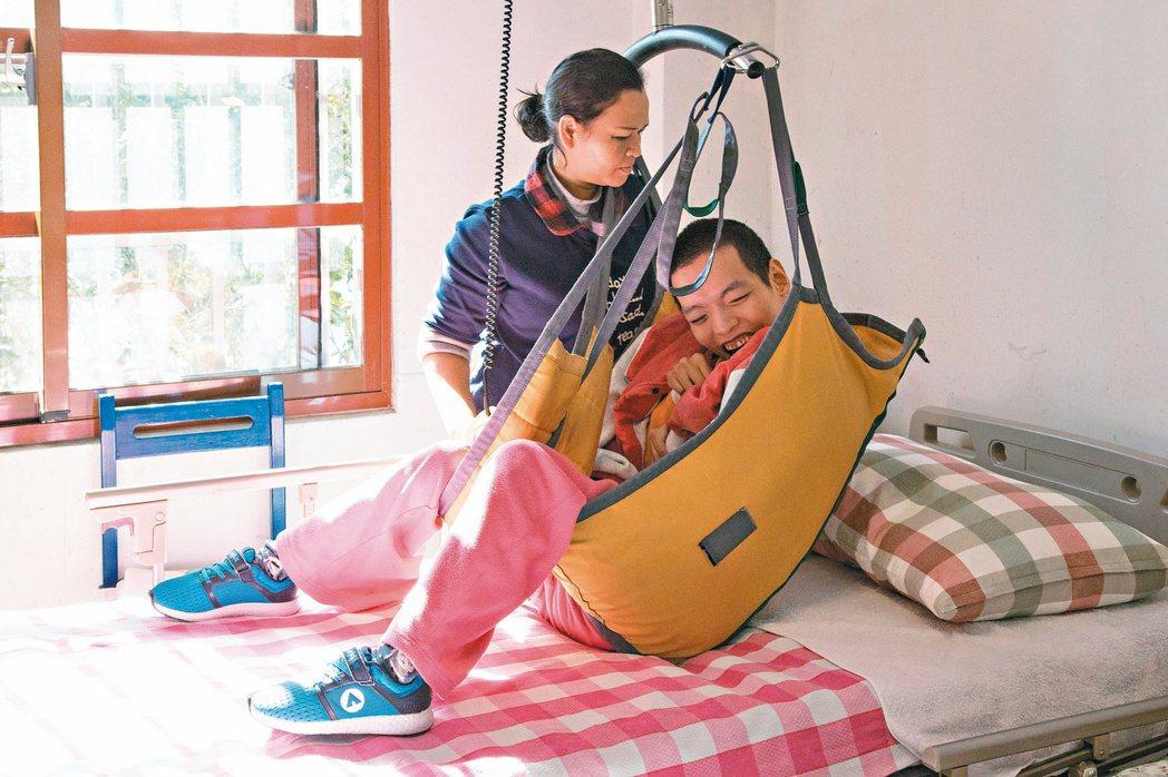 宜蘭縣特教資源中心前主任王宜忠的兒子從小癱瘓,他在房裡安裝了懸吊式移位機(圖),...