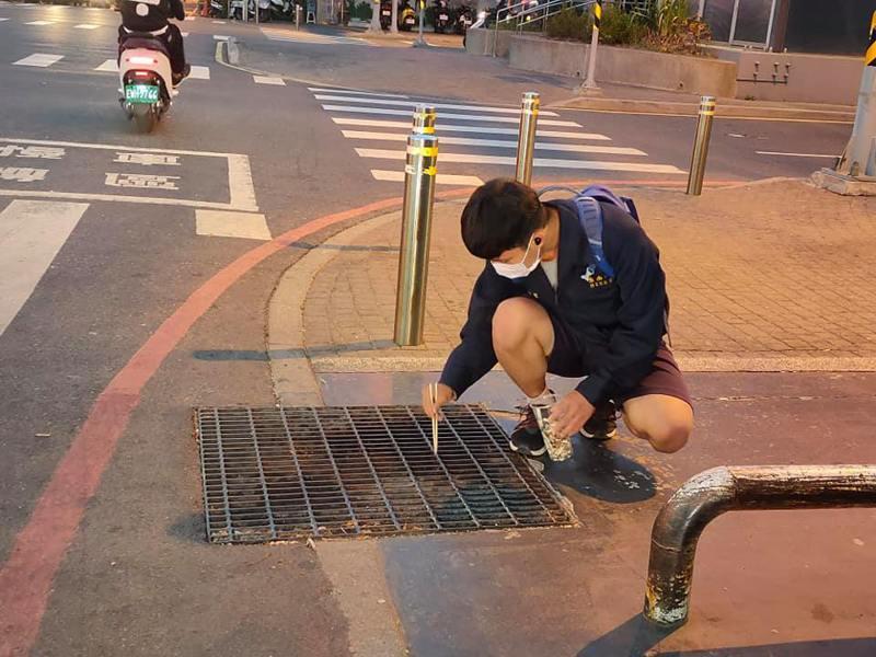 台南一中的學生蹲在地上用筷子撿菸蒂。圖/截自吳勝宏臉書
