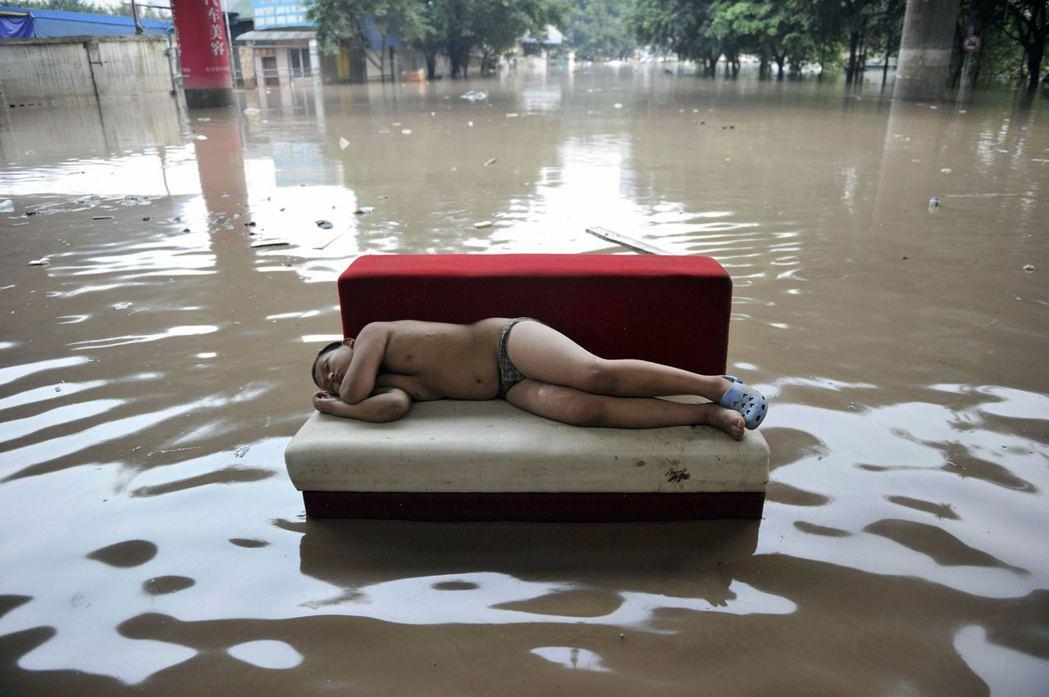 2010重慶大淹水,一名男孩在災區中睡覺休息。 圖/路透社
