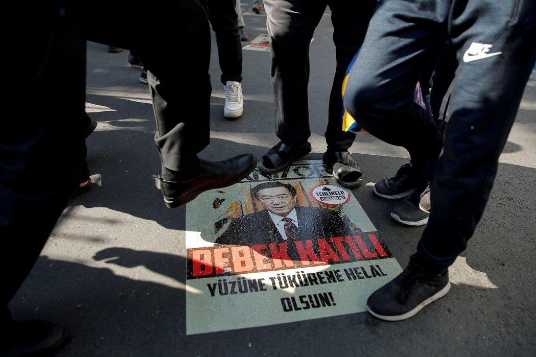 圖為 2020 年,維吾爾族示威者在中國駐伊斯坦布爾領事館前抗議,踩著一張印有陳...