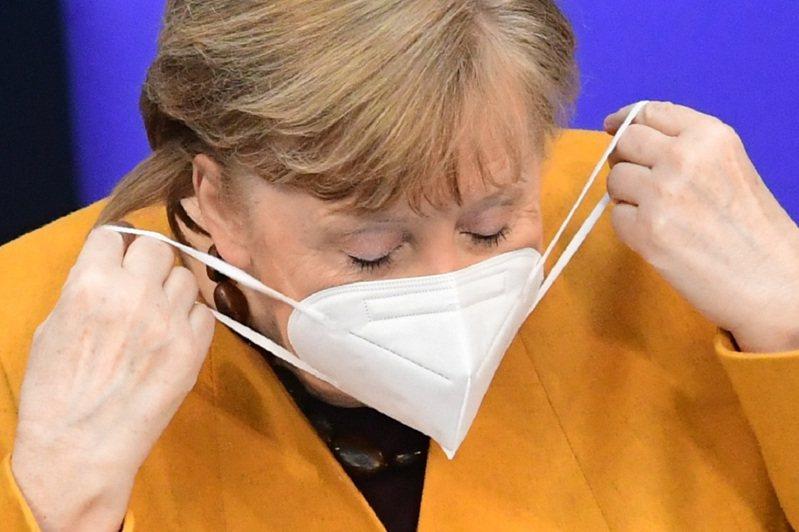 德國總理梅克爾24日赴德國聯邦議院(Bundestag)備詢,準備脫口罩走上講台發言。歐新社