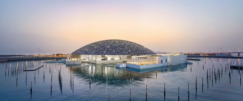 阿布達比羅浮宮建築外觀融合阿拉伯風格語彙與西方當代建築特色,呈現猶如懸浮水上的神秘發光體。 © Department of Culture and Tourism Abu Dhabi. 攝影:Hufton Crow