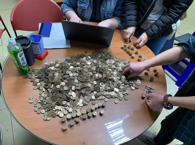 雇主支付薪資時,拿出2大袋8000多個1元硬幣。圖/取自移民移工服務中心