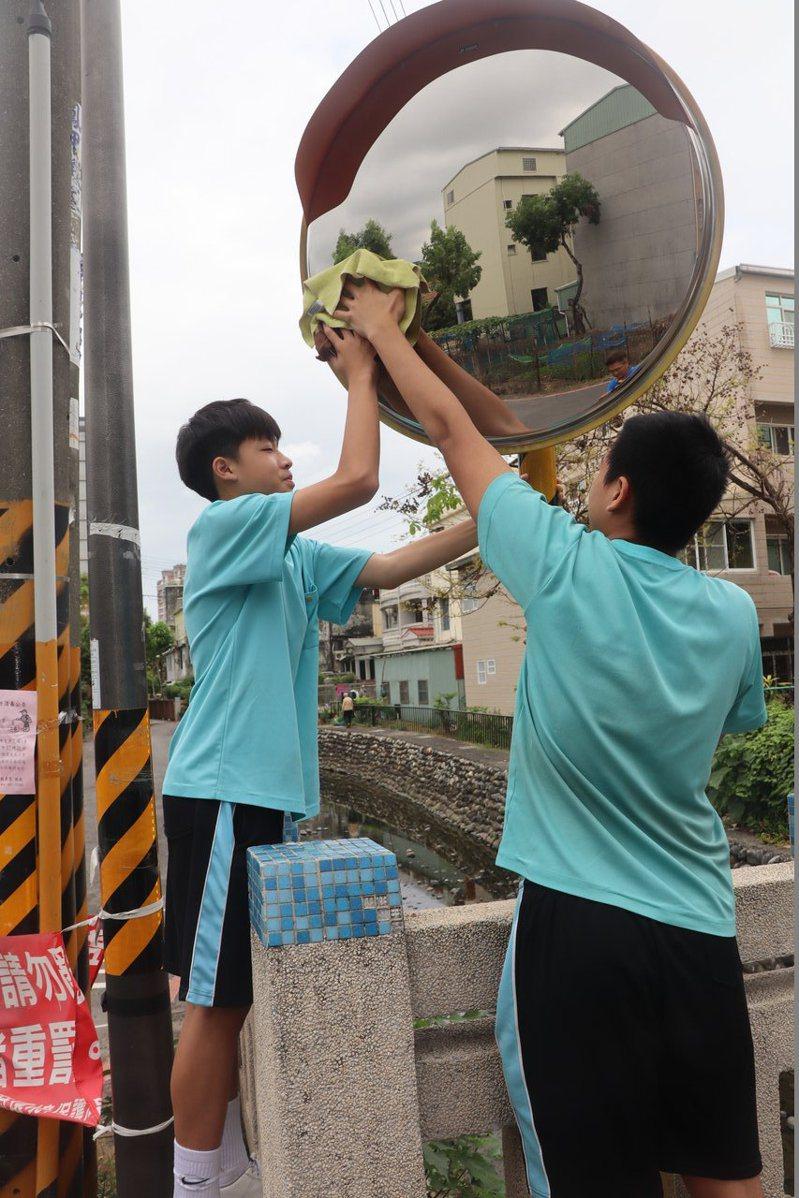 青年國中籃球隊學生擦拭轉角反光鏡,為社區盡一份心力。圖/高市教育局提供