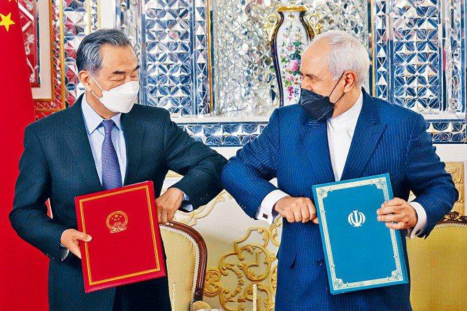 中國大陸國務委員兼外交部長王毅(左)與伊朗外長扎里夫在德黑蘭簽署合作協議。(星島日報)