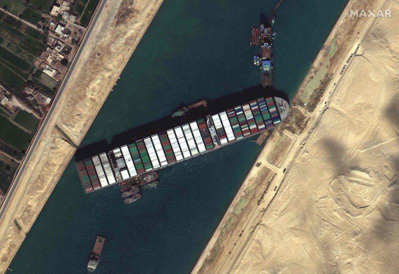 衛星影像顯示,拖船和挖泥船27日試圖讓在蘇伊士運河擱淺的長榮海運貨櫃輪長賜號脫困。法新社