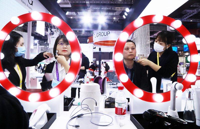 在第三屆中國國際進口博覽會的消費品展區,民眾在化妝品展台體驗新款美容儀。(中新社資料照)
